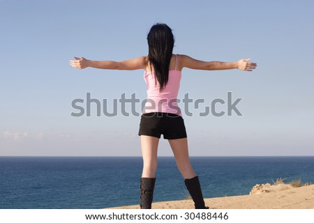 Nice girl at seaside standing open arms