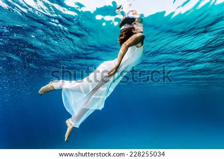 Nice girl emerges from the sea, swimming underwater, enjoying nice refreshing water, wearing long dress, summer vacation and travel concept  - stock photo