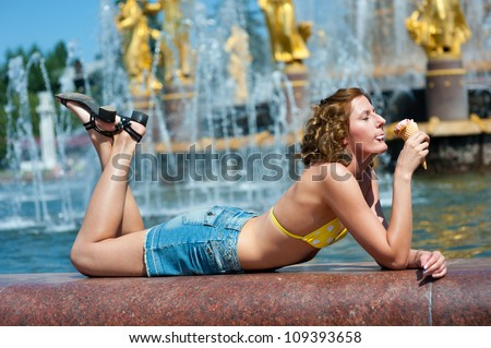 Nice girl enjoys the ice cream. Fountain in background. - stock photo