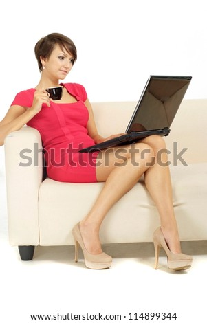 Nice girl in coral dress lying at home on the couch - stock photo