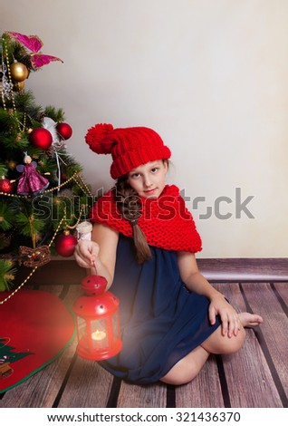 Nice girl sits with red lantern nearby decorative Christmas tree; cute child wearing warm red scarf and hat; empty space for your text - stock photo