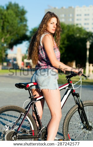 Nice girl sitting on bicycle at park