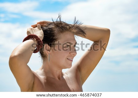 nice girl smiling at the beach with hand in the hair