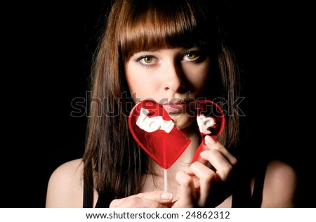 nice girl with a broken sweet in form of a heart - stock photo