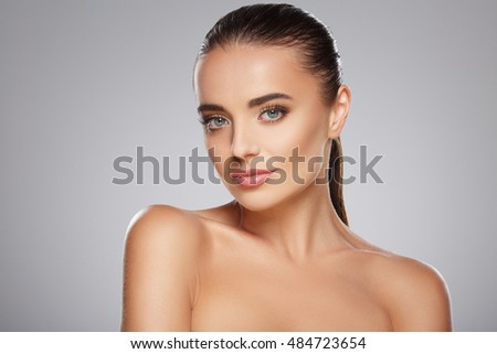 Nice girl with brown fixed hair behind, big eyes and naked shoulders posing at gray studio background, a model with light nude make-up, portrait, beauty photo.