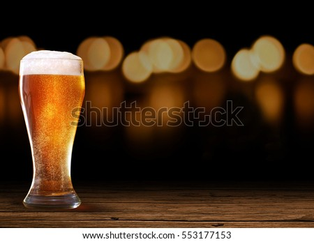 Nice Glass of Beer in left on the wooden rustic table with black and bokeh effect background at night, on a dark pub.
