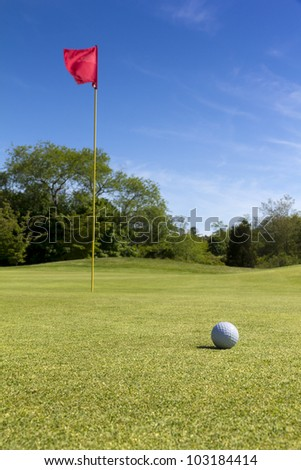 Nice golf field with flag and golf ball.