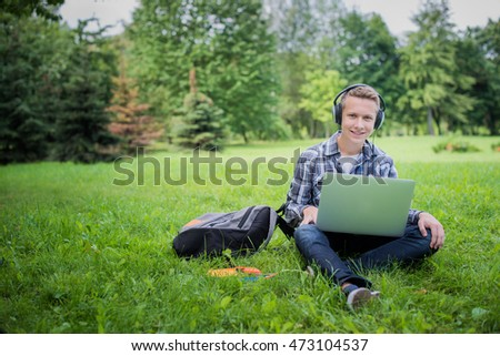 Nice guy in campus park  studying on his computer. Listening music in headphones. Looking in camera.