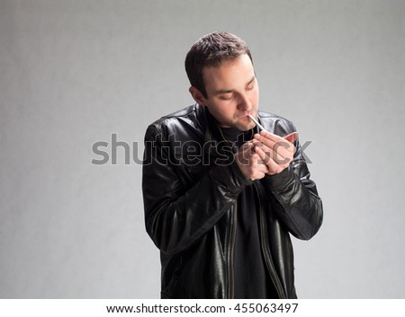 nice guy lights a cigarette gray background