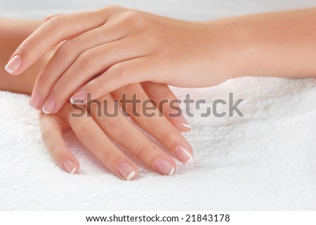 Nice hands on white towel. Soft manicure. - stock photo