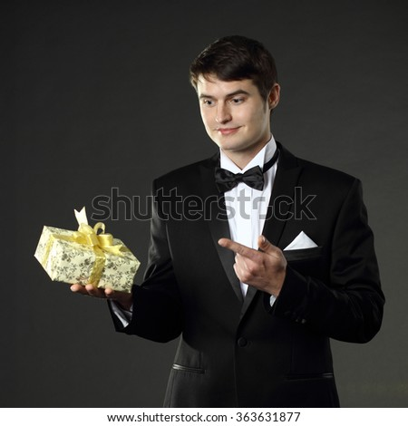 nice handsome man in a tuxedo gives a gift. On a black background.
