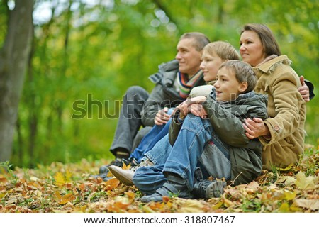 Nice happy family sitting in autumn park