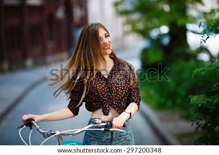 Nice happy girl with long fair hair is standing on the street on blouse and shorts with bicycle - stock photo