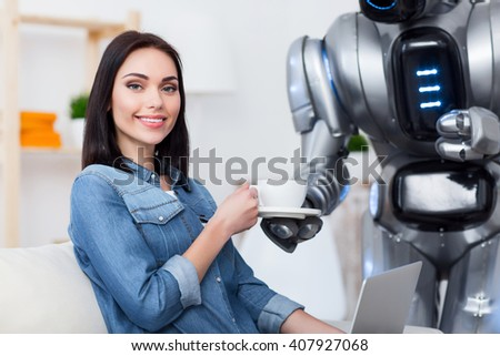 Nice house keeper. Cheerful delighted attractive girl sitting on the couch and using laptop while  getting cup of coffee from her robot  - stock photo