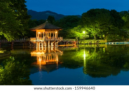 Nice japanese wooden gazebo is shortly after the sunset reflecting in the water. Nara, Japan.