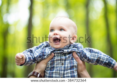 Nice joyful smiling blond little boy in father`s hands in air look away on blurred natural background, horizontal photo - stock photo