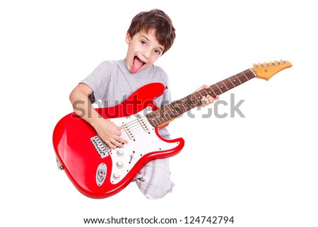 Nice kid playing a red guitar on the floor with his tongue out. The child is isolated on white. - stock photo
