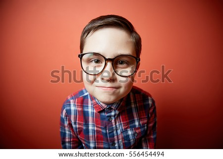 nice kid with big glasses on red background