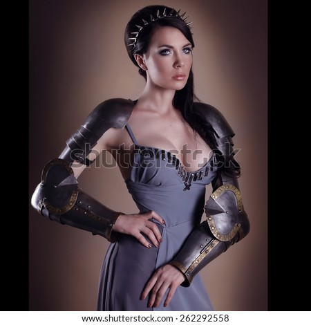 Nice lady in ancient armor posing in Joan of Arc style. portrait of a beautiful lady warrior, dark-haired girl in a gray dress. bright makeup, hairstyle, spikes.  - stock photo