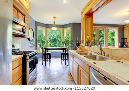Nice large beautiful wood kitchen with grey walls. - stock photo