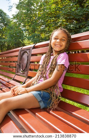 Nice little black girl sitting on the bench in park - stock photo