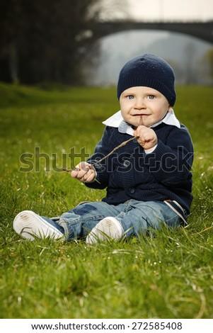 Nice little boy sitting on meadow - stock photo