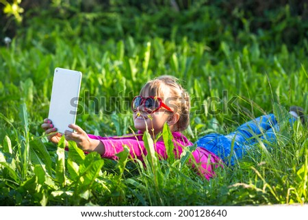 Nice little girl does selfie on a tablet PC lying in the grass. - stock photo