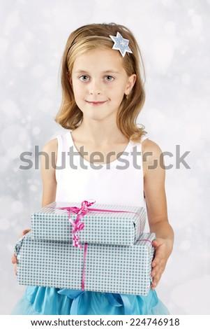 Nice little girl holding christmas presents - stock photo