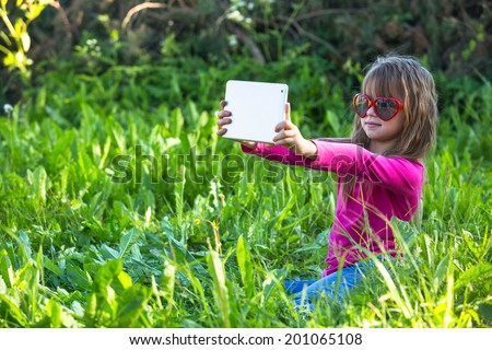 Nice little girl in nature and taking self portrait (selfie) on a tablet PC. - stock photo