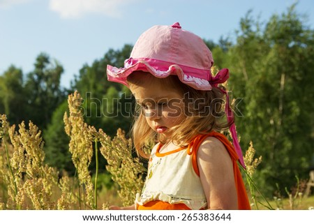 Nice little girl playing in meadow at sunset in summer day