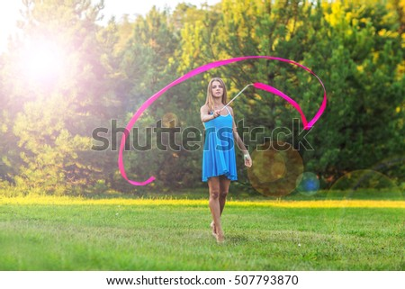 nice little girl playing with gymnastic ribbons in a clearing in nature. Woman with gymnastic tapes played in a summer park. She is dressed in a blue short dress, pink ribbon