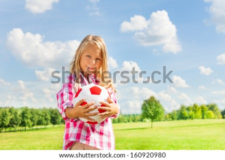 Nice little 6 years old blond cute girl in pink shirt with soccer ball - stock photo