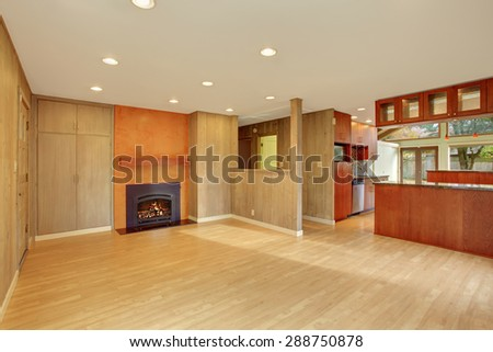 Nice living room with hard wood floor and fireplace. Cherry wood kitchen with open floor plan. - stock photo