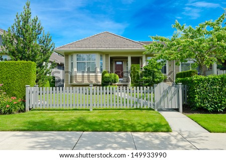 Nice looking house behind the wooden fence at the empty street in the suburbs of Vancouver, Canada. - stock photo