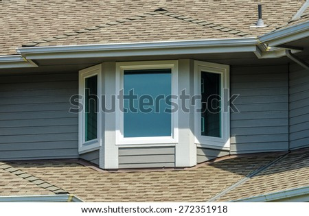 Nice looking window at the roof of the house. - stock photo