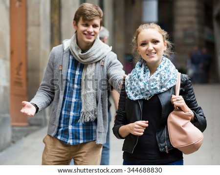 Nice-looking  young spanish male student chasing pleased girl on outdoor date. focus on girl - stock photo