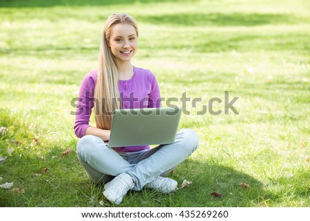 Nice looking young woman outdoors. Woman using laptop and looking at camera. Beautiful green park as a background