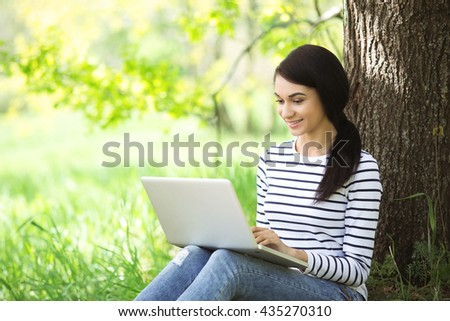 Nice looking young woman outdoors. Woman using laptop. Beautiful green park as a background