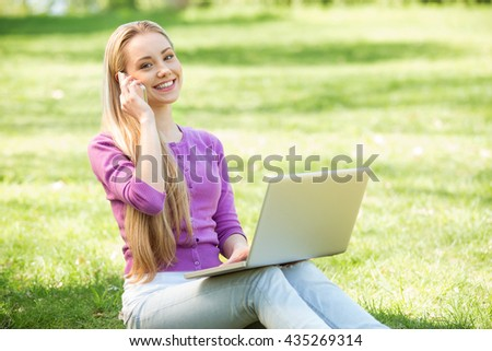 Nice looking young woman outdoors. Woman using laptop with mobile phone and looking at camera. Beautiful green park as a background