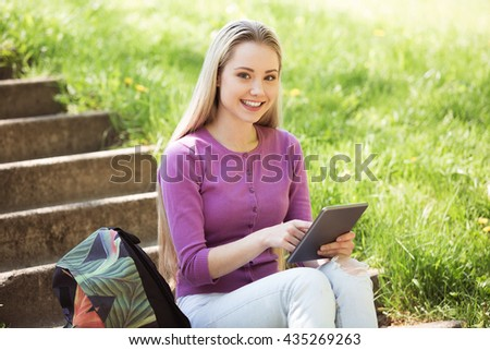 Nice looking young woman outdoors. Woman using tablet computer and looking at camera. Beautiful green park as a background