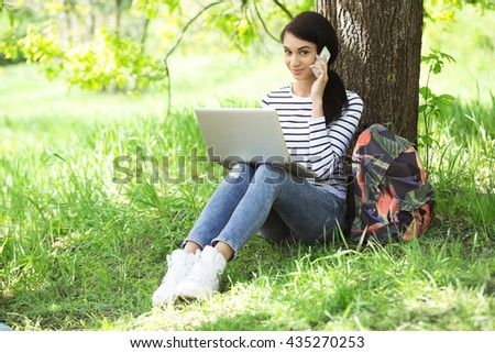 Nice looking young woman outdoors. Woman with backpack using laptop and mobile phone. Beautiful green park as a background