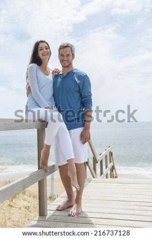 nice loving couple standing on a wood way in front on the sea