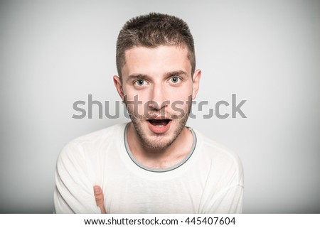 nice man opened his mouth in surprise, isolated on a gray background - stock photo