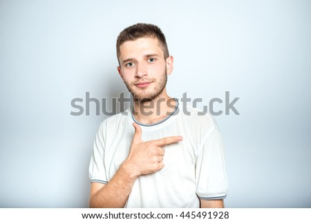 nice man points a finger to the side, isolated on a gray background - stock photo