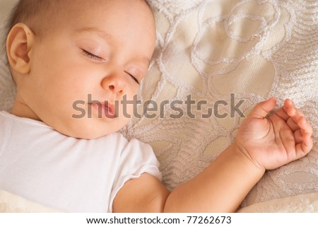 nice newborn sleeps on a white bed