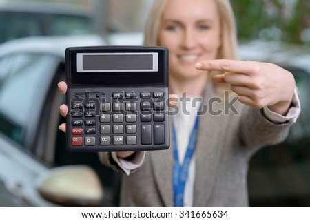 Nice offer. Young attractive saleswoman is holding a calculator and pointing at incredibly nice price for a car. - stock photo