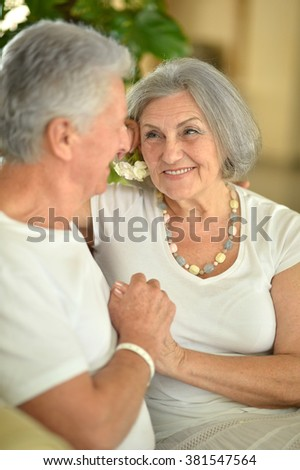 Nice old couple went to a resort vacation,sitting in room on sofa - stock photo