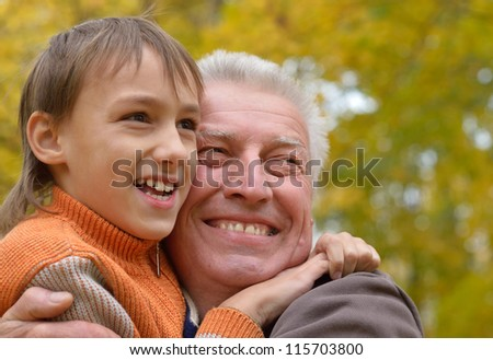 nice old man with kid resting in the autumn park