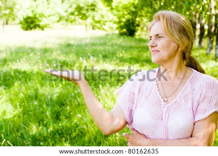 nice old woman stands in a park