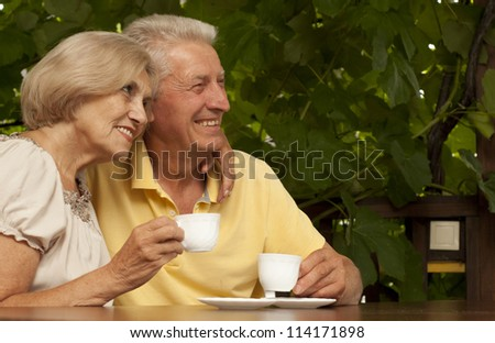 Nice older couple sitting at a table at home on the veranda - stock photo